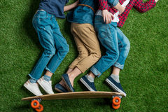 Children pretending standing on skateboard on green grass Royalty Free Stock Photo