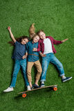 Children pretending standing on skateboard on green grass Royalty Free Stock Photography