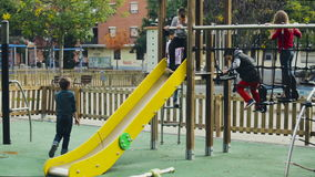 Children of primary school age are having fun on the slide. Cheerful boy and girls in elementary school age having fun on slide stock video footage