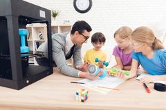 Children print different items on a 3d printer with a teacher. stock image