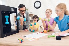 Children print different items on a 3d printer with a teacher. stock photo