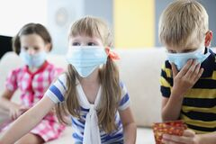 Children in protective medical masks playing board games at home