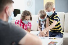 Children in protective medical masks playing board games with their parents at table