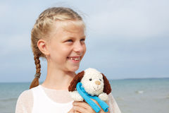 Children psychology. The little beautiful girl embraces an amusi Stock Images