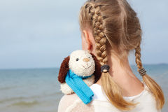 Children psychology. The little beautiful girl embraces an amusi Royalty Free Stock Images