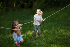 Children pulling the rope outdoors Stock Images