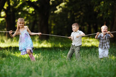 Children pulling the rope outdoors. Photo of children pulling the rope outdoors Royalty Free Stock Photo