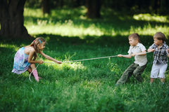 Children pulling the rope outdoors. Photo of children pulling the rope outdoors Royalty Free Stock Photos