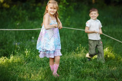 Children pulling the rope outdoors Stock Photos