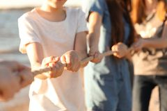 Children pulling rope during tug of war game outdoors. Closeup. Summer camp Royalty Free Stock Photo