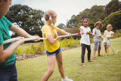 Children pulling a rope in tug of war Stock Photo