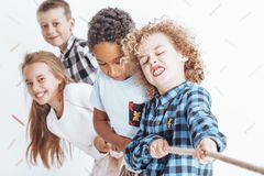 Children pulling the rope. Using a team effort Stock Photos