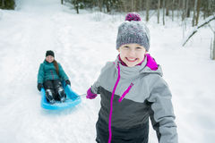 Children Pulling Sledge Through Snowy Landscape Stock Images
