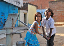Children pumping water into the bucket. India Royalty Free Stock Photography