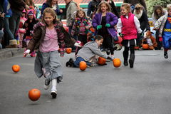 Children Pumpkin bowling down Caroline Street,Saratoga Springs,New York,October,2013. Lines of children in Halloween costumes joining in the fun of pumpkin Royalty Free Stock Images