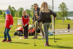 Children on a putting green instructed by woman Royalty Free Stock Photography