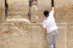 Children is putting a praying note in a gap of the wailing wall Stock Photography