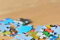 Children& x27 ; puzzles de s sur un fond en bois Images stock