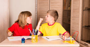 Children quarreling. Sister teasing brother while doing homework. Together Royalty Free Stock Photo