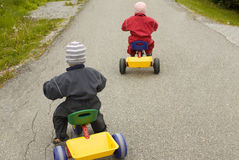 Children racing. On tricycles, child in red leading in front of child in blue Royalty Free Stock Image