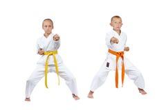 Children in rack kiba dachi are beating punch gyaku-tsuki Stock Image