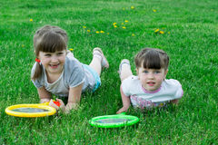 Children with rackets on the grass. Funny kids lie on the grass with a badminton racket stock images