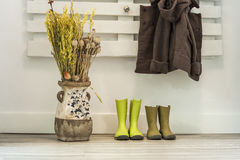 Children rainy boots, brown coat and a vase with dried flowers. Home entrance stock photography