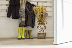 Children rainy boots, brown coats, scarf and a vase with dried f. Lowers. Open door entrance royalty free stock photography