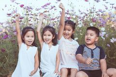 Children raise hands and playing together in the cosmos flower Stock Image