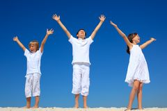 Children with raised hands. Three children wearing white clothes with arms outstretched as they stand on a beach against a blue sky Stock Photography