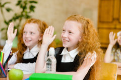 Children raising hands knowing the answer to the question Stock Photography