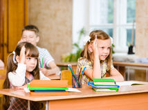 Children raising hands knowing the answer to the question Royalty Free Stock Image
