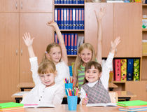 Children raising hands knowing the answer to the question Royalty Free Stock Photography