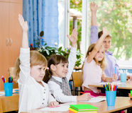 Children raising hands knowing the answer to the question Royalty Free Stock Images