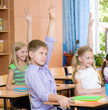 Children raising hands knowing the answer to the question Stock Photo