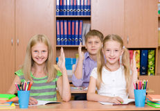 Children raising hands knowing the answer to the question Royalty Free Stock Photos
