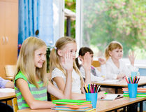 Children raising hands knowing the answer to the question Stock Photos