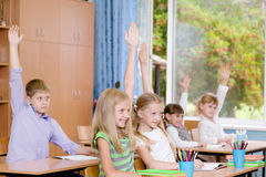 Children raising hands knowing the answer to the question Royalty Free Stock Photo