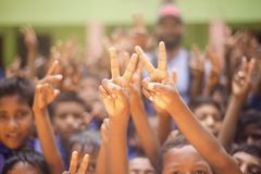 Children raising their hands showing victory sign. Unique photo royalty free stock photos