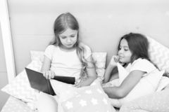 Children read book in bed. Stories every kid should read. Family tradition. Girls best friends read fairy tale before. Sleep. Best books for kids. Reading stock images