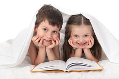 Children read a book in bed. Under the blanket Stock Photos