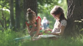 Children read a book outdoors sitting on the grass near a tree. Two little girls have fun together stock video