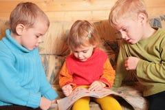 Children read book on sofa Stock Photo