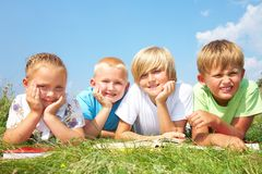 Children read  books in grass Royalty Free Stock Images