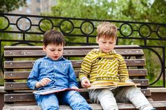 Children read books outdoors royalty free stock image