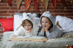 The children read a great book with Christmas tales. Christmas Holidays. Two children, brother and sister lie on big bed and read Christmas tales. Children Royalty Free Stock Photo