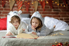 The children read a great book with Christmas tales. Stock Image