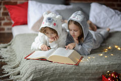 The children read a great book with Christmas tales. Stock Images