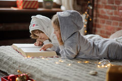 The children read a great book with Christmas tales. Stock Photos