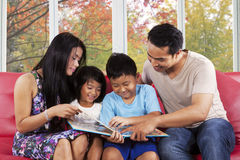Children read a story book with parents Royalty Free Stock Photo